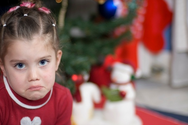 In front of a Christmas tree sits a girl who is frowning - Christmas snowmen in the background