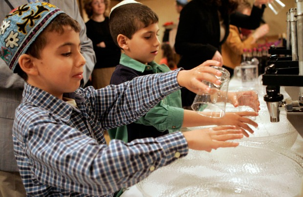 02 Apr 2007, Clinton, New Jersey, USA --- Brothers Ilan, 8, left, and Jeremy Samoun, 7, of Flemington perform customary hand washing during a community Passover Seder held by Chabad of Hunterdon at the Holiday Inn hotel in Clinton. --- Image by © George Olivar/Star Ledger/Corbis