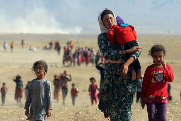 Displaced people from the minority Yazidi sect, fleeing violence from forces loyal to the Islamic State in Sinjar town, walk towards the Syrian border, on the outskirts of Sinjar mountain, near the Syrian border town of Elierbeh of Al-Hasakah Governorate August 11, 2014. Islamic State militants have killed at least 500 members of Iraq's Yazidi ethnic minority during their offensive in the north, Iraq's human rights minister told Reuters on Sunday. The Islamic State, which has declared a caliphate in parts of Iraq and Syria, has prompted tens of thousands of Yazidis and Christians to flee for their lives during their push to within a 30-minute drive of the Kurdish regional capital Arbil. Picture taken August 11, 2014. REUTERS/Rodi Said (IRAQ - Tags: POLITICS CIVIL UNREST TPX IMAGES OF THE DAY) FOR BEST QUALITY SEE RTR43BMZ - RTR426FA